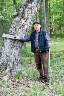 Standing next to a tree in the forest where my cousin Adam built a ladder 30 years ago.